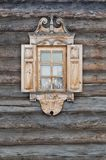 Window with carved architraves in a wooden hut. Window with carved architraves in a wooden hut Royalty Free Stock Images