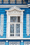 Window with carved patterns on old blue wooden house Royalty Free Stock Image