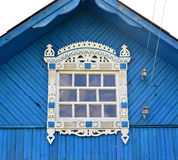 Window with carved platbands under a roof of the blue house Royalty Free Stock Photography