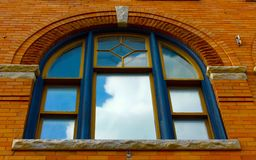 Window Casing. Decorative window casing on an old brick building with clouds and blue sky reflection Royalty Free Stock Image