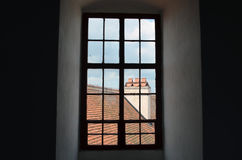 Window in the castle tower. View through wooden window in the castle tower on the roof covered with tiles, Kromeriz, Czech Republic Stock Photo