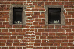 Window Ceramics. Two windows in a red brick wall with ceramic pots Stock Images