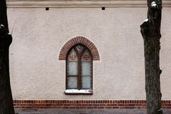 A window of a church on a blank wall between two trees royalty free stock photos
