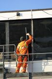 Window cleaner. Worker in bright overalls giving airport control tower a clean Royalty Free Stock Images