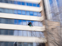 Window Cleaner on high-rise. Dramatic zoom of a Window Cleaner cleaning windows on a high rise building Royalty Free Stock Photo
