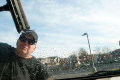 Window cleaner. Man cleaning window of car Royalty Free Stock Image