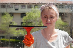 Window cleaner using a squeegee to wash a window Stock Photography