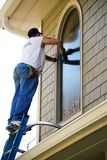 Window Cleaner/Washer. Man on a ladder washing windows on a house. Construction cleanup or spring cleaning theme stock image