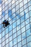 Window cleaner at work. Window cleaner hanging on rope at work on skyscraper Royalty Free Stock Images