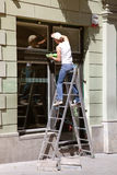 Window cleaner working on a ladder Royalty Free Stock Photos