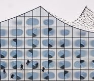 Window Cleaners cleaning the Elbphilharmonie. A number of window cleaners climb down the glass front of Hamburg`s Elbphilharmonie to sweep the windows Stock Photography