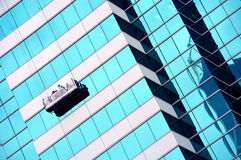 Window cleaners in gondola. Two window cleans in a gondola cleaning windows of a commercial building Royalty Free Stock Photography