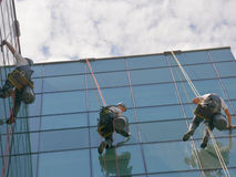 Window cleaners on office building, photo taken 20.05.2014. Professional, window cleaners alpinist climber, washing windows on business building, photo taken 20 Stock Image