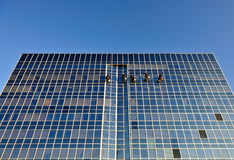 Window cleaners on skyscraper stock images