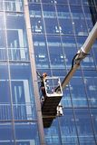 Window cleaners working on a modern high rise glass building. Copenhagen, Denmark - August 17, 2018: Window cleaners working on a modern high rise glass building royalty free stock image