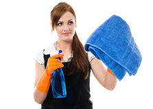 Window cleaning. Pretty young woman in orange protective gloves cleaning window with spray and towel Stock Images