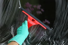 Window cleaning. Housework with red squeegee for glass, window cleaning Stock Photos