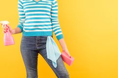 Window cleaning chore woman atomizer sponge cloth. Window cleaning. Domestic chores. Woman holding atomizer and sponge with cloth in pocket. Copy space on yellow stock image
