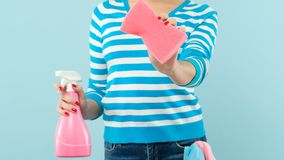 Window cleaning chore woman atomizer sponge cloth. Window cleaning. Domestic chores. Woman holding atomizer and sponge with cloth in pocket. Copy space on blue stock image