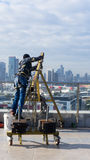 Window cleaning employee with work tools and city background. Royalty Free Stock Photo