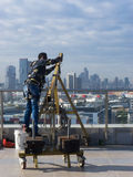 Window cleaning employee with work tools and city background. Stock Photography