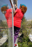 Window cleaning. Female with a blue scarf over long curly brown hair wearing red t-shirt and purple slacks, a wrist band, cleaning window hanging outside and her Stock Photo