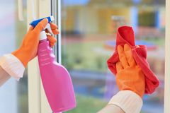 Window cleaning. Hands in gloves with a spray and a rag royalty free stock photography