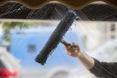 Window cleaning. A soapy window with a squeegee cleaning the glass stock photography