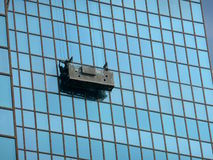Window cleaning suspended platform. Suspended platform or cradle for cleaning windows of a skyscraper Stock Photos