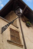 Window closed by shutters, with lamp and gutter. An closed window with brown shutters, with a lamp and a gutter on the same wall Stock Photo