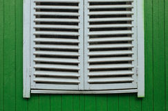Window with closed white jalousies on green wall Royalty Free Stock Photos