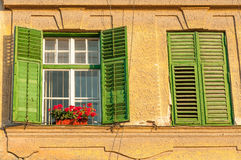 Window With Closed Wooden Shutters. Decorated With Fresh Flowers Stock Photo