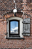 Window on clouds and sky. An old window with one wooden shutter on a red brick wall, opened to a view of blue sky and clouds Royalty Free Stock Image
