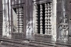 Window Colonettes and bas reliefs at 12th century Ankgor Wat temple. Scene around the Angkor Archaeological Park. The site contains the remains of the different Royalty Free Stock Images