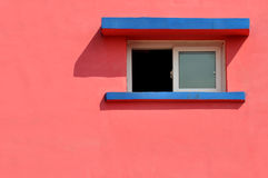 Window on color wall. A small window and shadow on pink color wall, shown as geometric shape and color of the architecture Stock Photos
