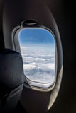 The window of a commercial airplane flying high Royalty Free Stock Photography