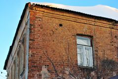 The window on the corner the old brick building, roof covered with snow on blue sky background. Branches without leaves royalty free stock photography