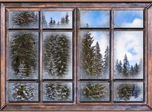 The window is covered with ice frost. Winter landscape view from the window is covered with ice frost Stock Photo