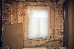 Window covered by polyethylene and brick wall with plastic plumbing pipe in an apartment is under construction, overhau royalty free stock photography