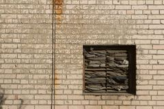 Window covered with rags in a brick wall. And rusty wire Stock Photography