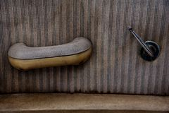 Closeup Interior Door of Old Vintage Automobile window hand crank upholstery and armrest Stock Image
