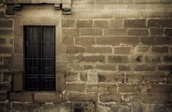 Window on creepy stonewall Stock Photo