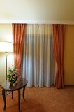Window with curtains. A window in a room with curtains and a table and lamp nearby Royalty Free Stock Photography