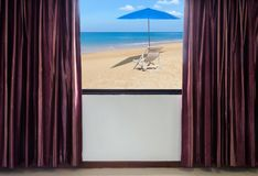 Window with curtains and blinds looking out the window frame meet seaside view. With white wooden beach chair and blue parasol Stock Images