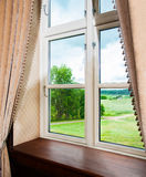 Window with curtains. Window draped in curtains, with a view to nature Royalty Free Stock Photo