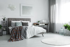 Window with curtains. Window with grey and white curtains in spacious room with bed Stock Images