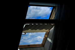 The window of the dark attic, open. A view of a clear blue sky with clouds. Contrast, darkness, light Royalty Free Stock Photo