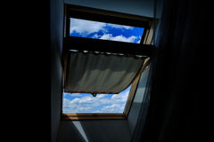 The window of the dark attic, open. A view of a clear blue sky with clouds. Contrast, darkness, light Stock Photography