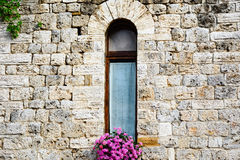 Window decorated with a pot of pink flower. In the historic center of San Gimignano, Tuscany, Italy royalty free stock images