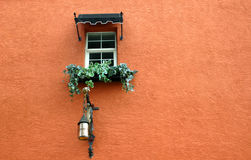 Window Detail. Window on Spanish building, with black awning, flowers in window box and decorative light fixture royalty free stock images